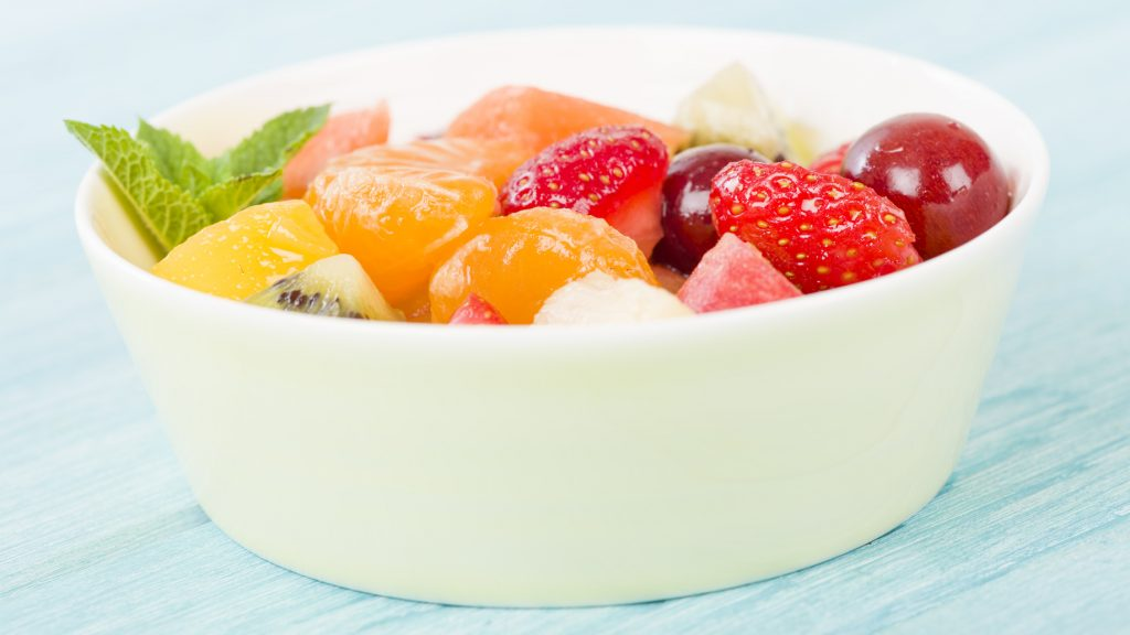 Fruit Salad - Bowl of fresh fruit salad on a blue background.