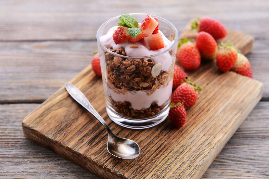 Healthy layered dessert with muesli and berries on table